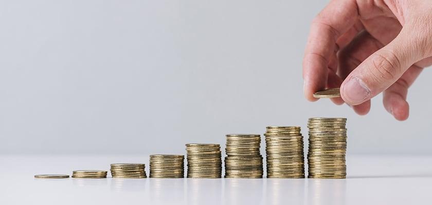 Un uomo impila monete in diverse colonne di denaro