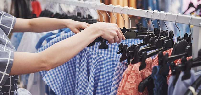 A woman searches for clothes to buy in a store